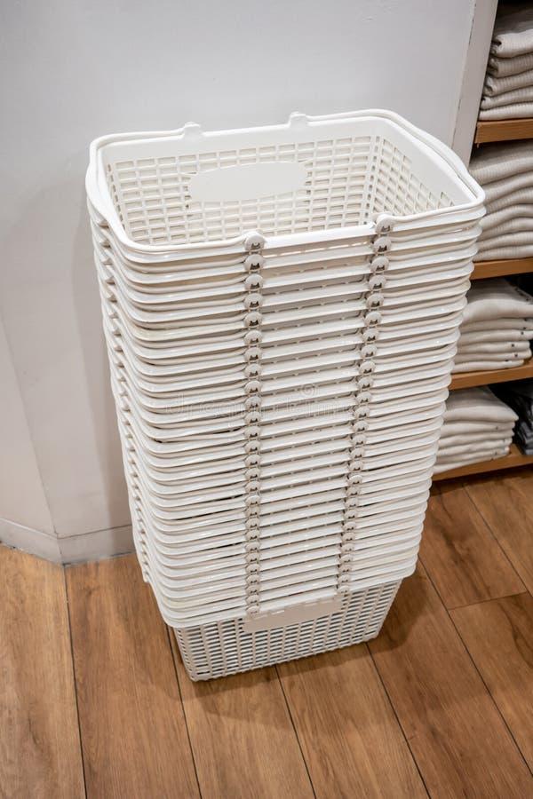 堆在木地板上的白色篮子在衣物零售店 库存图片