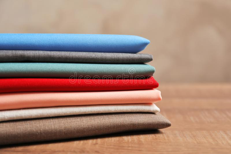 堆在木桌上的五颜六色的织品 图库摄影