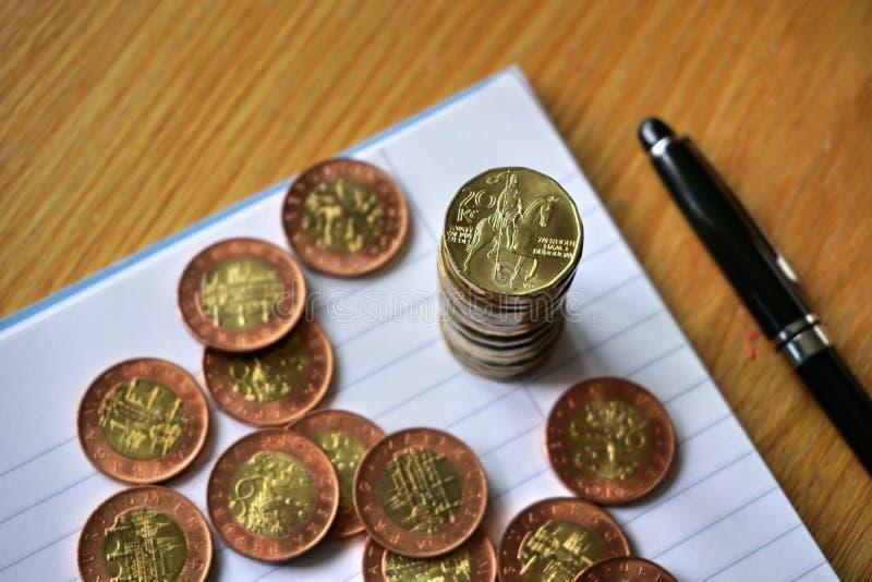 堆在木桌上的硬币与一枚金黄捷克冠硬币按20 CZK的价值在上面的 免版税库存照片