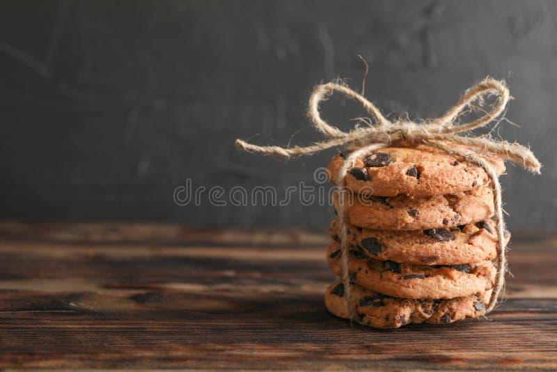 堆在木桌上的鲜美巧克力曲奇饼 免版税库存照片