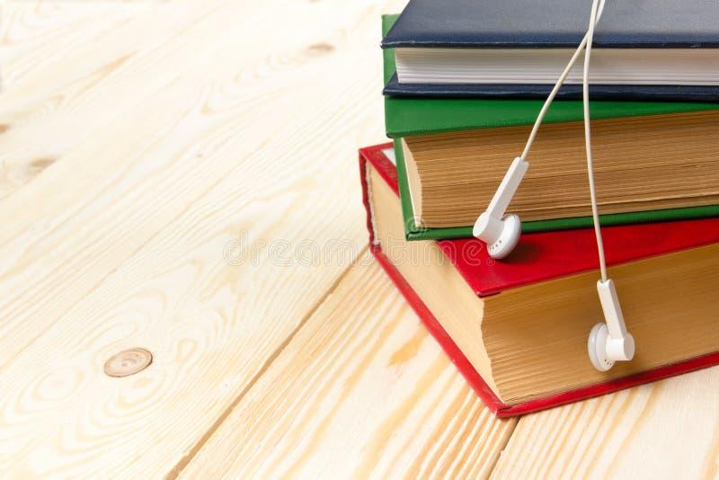 堆在木桌和耳机上的五颜六色的书 audiobook书概念耳机 免版税库存照片