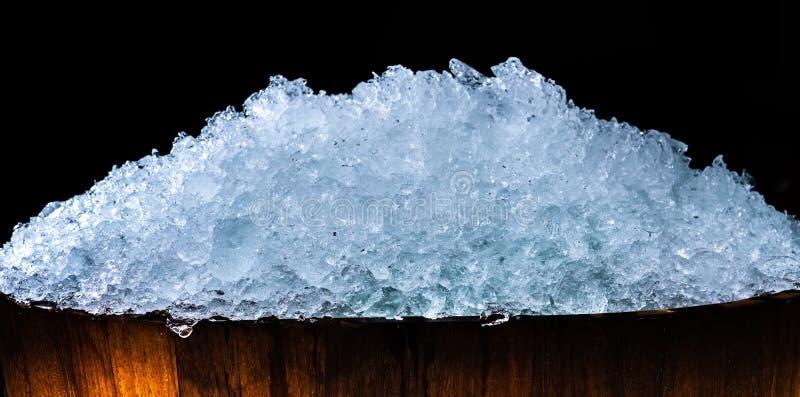 堆在木桶的被击碎的冰块在与拷贝空间的黑暗的背景 饮料的被击碎的冰块前景,啤酒 图库摄影
