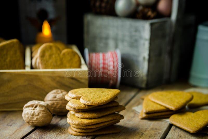 堆在木箱子的家庭焙制的圣诞节姜饼曲奇饼、灼烧的蜡烛、红色和白色丝带、杉木锥体和五颜六色的中看不中用的物品 免版税图库摄影