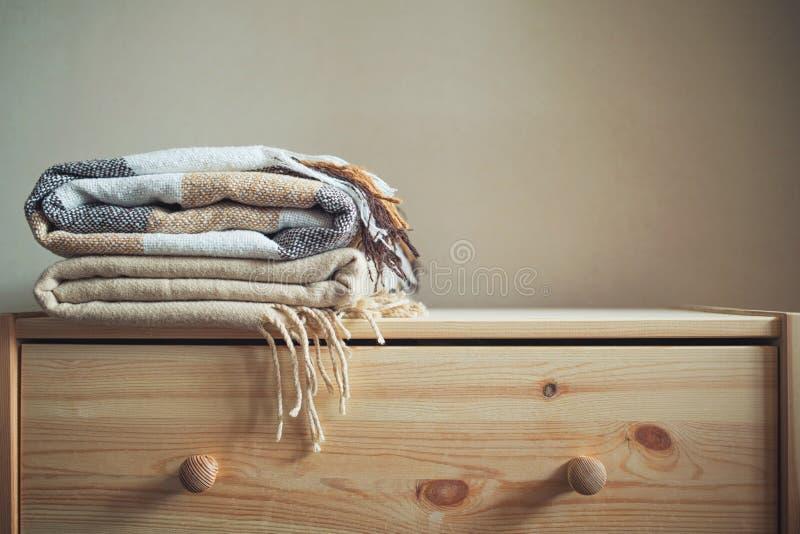 堆在木胸口的米黄方格的羊毛毯子 库存照片