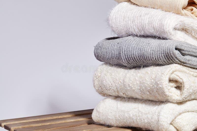 堆在木表上的时尚温暖的毛线衣 秋天和冬天羊毛衣裳 被编织的毛线衣或夹克 嫩颜色 免版税库存照片