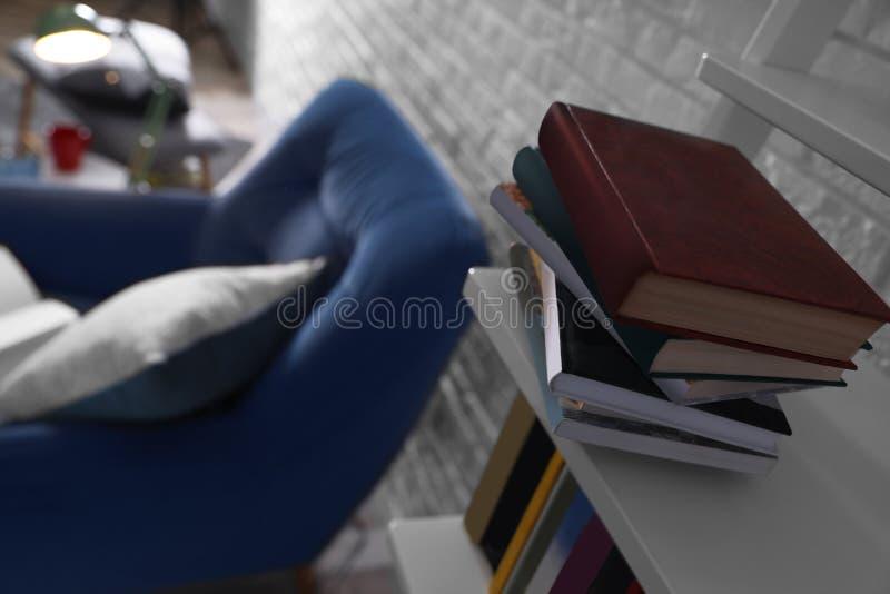 堆在架子的不同的书在屋子里 免版税库存照片