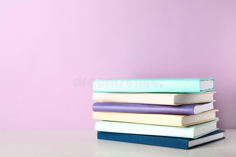 堆在架子的书反对颜色背景 库存图片