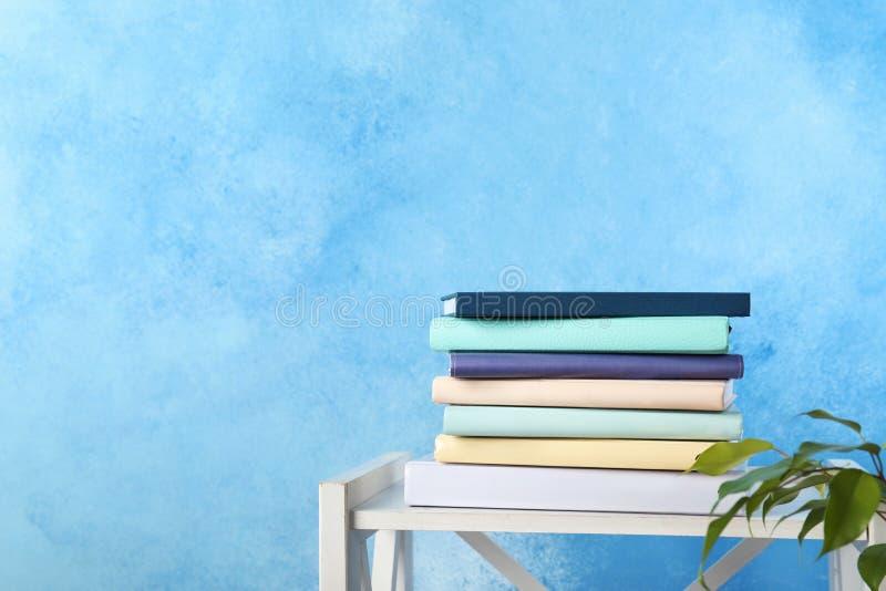 堆在架子的书反对颜色背景 免版税图库摄影