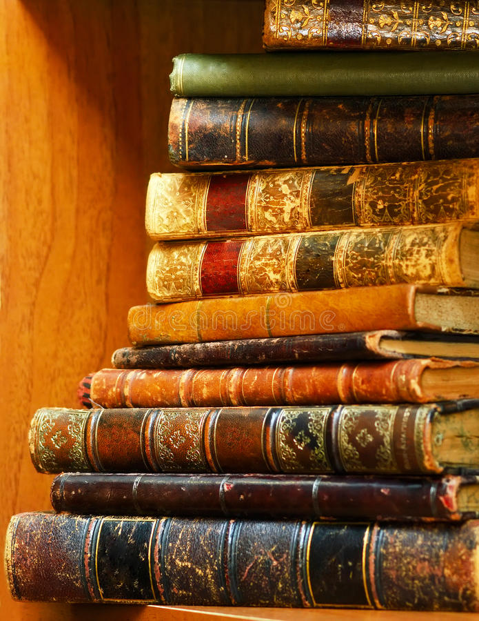 堆在架子的古色古香的书 免版税库存图片