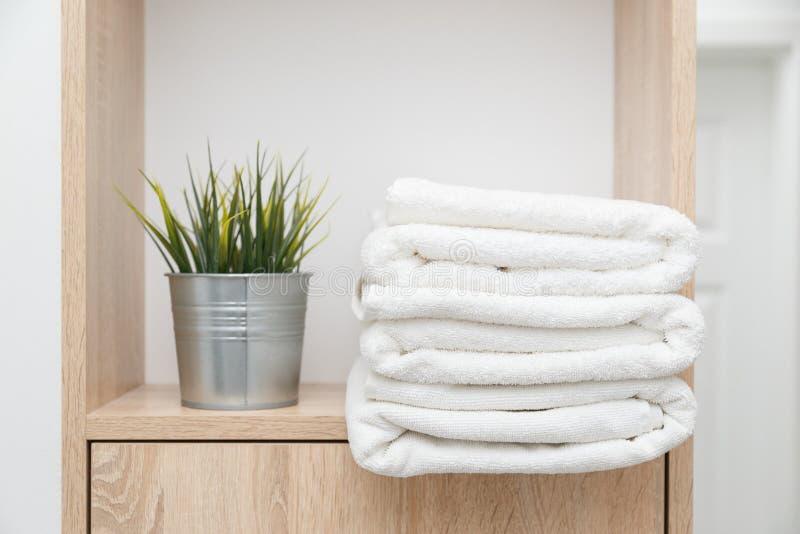 堆在架子的清洁毛巾与在桶的绿色 免版税库存照片
