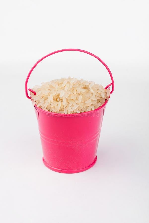 堆在桃红色桶的米五谷在白色背景 库存图片