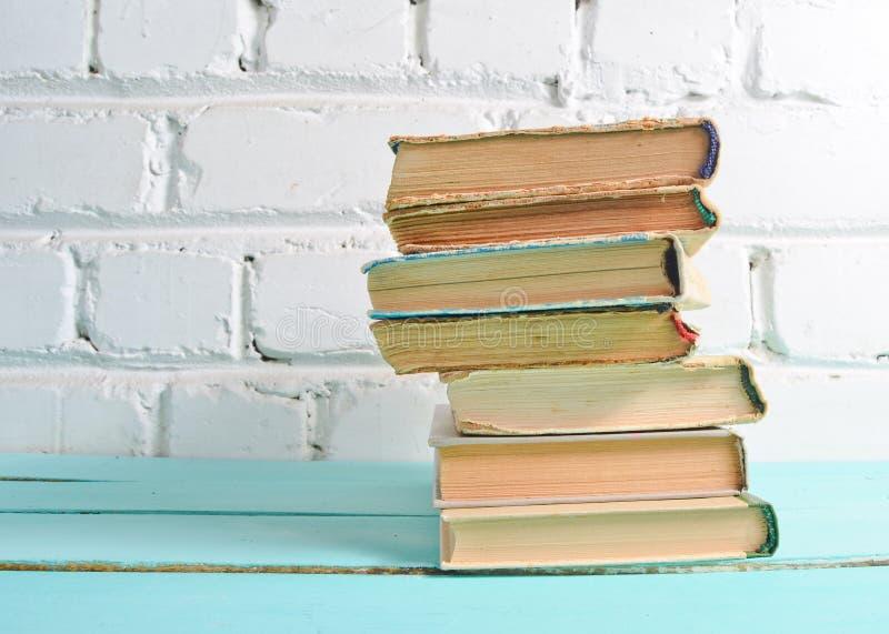 堆在桌上的古色古香的书对一个白色砖墙 学校概念,教育 库存图片