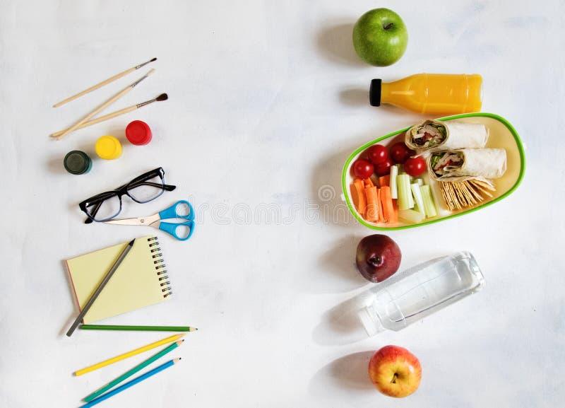堆在桌,笔记薄上的各种各样的文具,上色了铅笔,统治者,标志,整平机,文本的空间 可口学校午餐箱子 库存图片