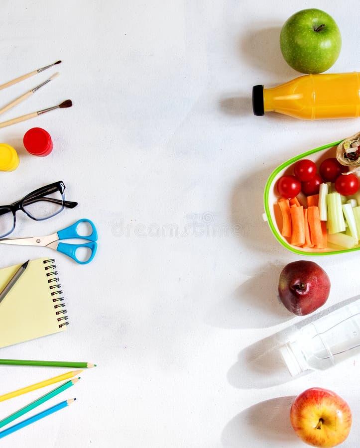堆在桌,笔记薄上的各种各样的文具,上色了铅笔,统治者,标志,整平机,文本的空间 可口学校午餐箱子 免版税图库摄影