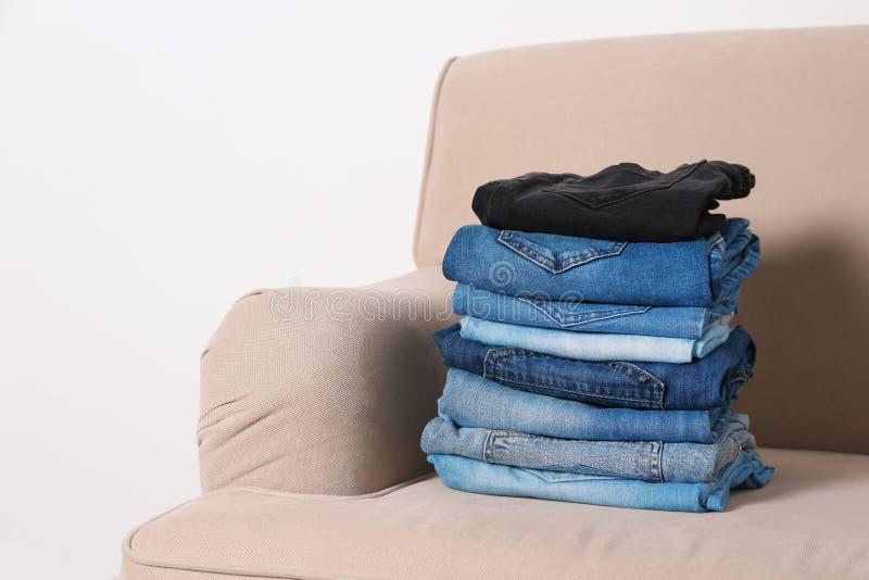 堆在沙发的不同的牛仔裤 免版税库存图片