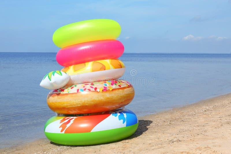 堆在沙滩的不同的明亮的可膨胀的圆环在海附近 库存图片