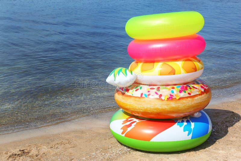 堆在沙滩的不同的明亮的可膨胀的圆环在海附近 库存照片