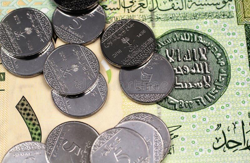 堆在沙特阿拉伯人的五枚halala硬币一里亚尔钞票 库存照片