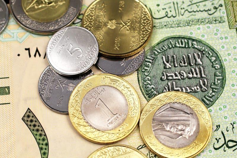 堆在沙特阿拉伯人的被分类的沙特硬币一里亚尔钞票 免版税库存照片