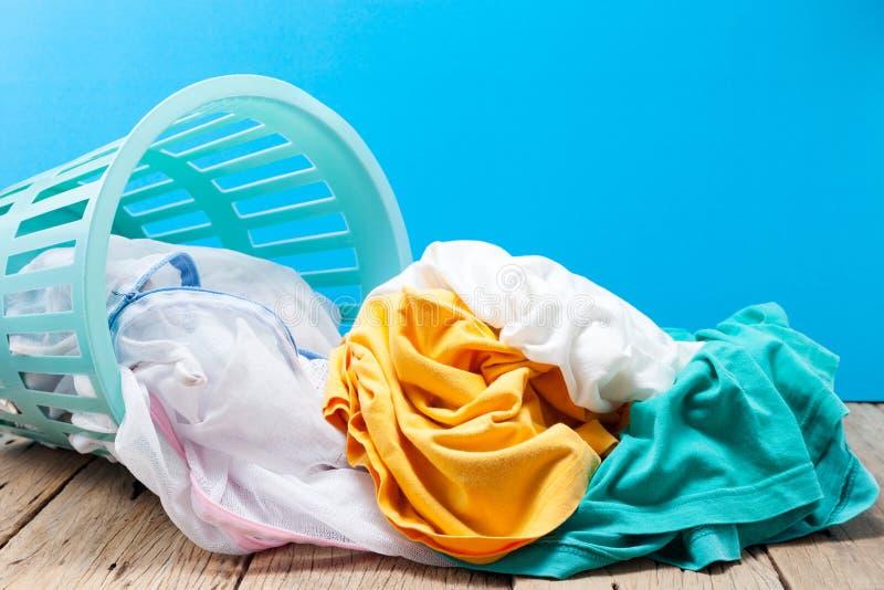 堆在洗涤的篮子的肮脏的洗衣店在木,蓝色backgroun 库存图片