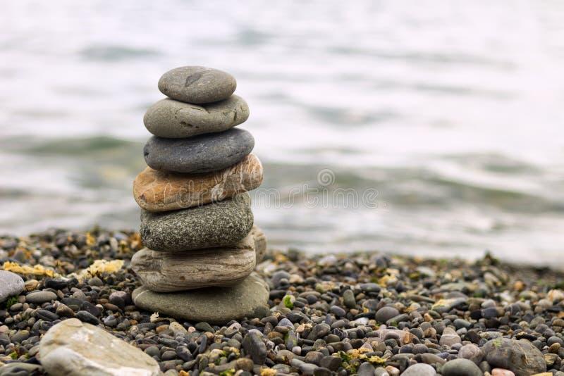 堆在海滩的禅宗石头 石头金字塔在海滩的 禅宗凝思背景-平衡的石头堆关闭 免版税图库摄影