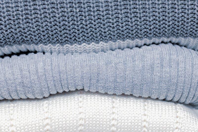 堆在淡色的舒适舒适的亲切被编织的毛线衣,舒适家常衣裳概念 库存照片