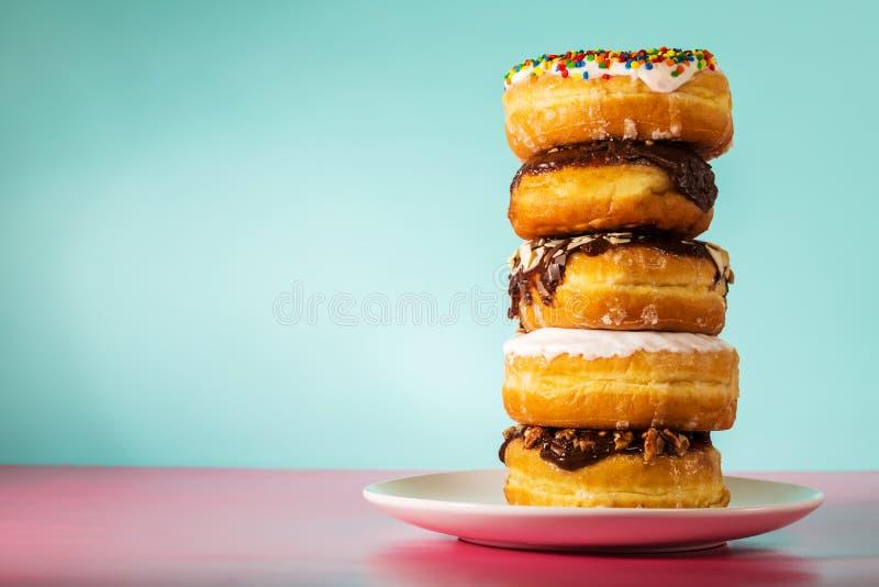 堆在淡色蓝色和桃红色背景的被分类的油炸圈饼 免版税库存照片