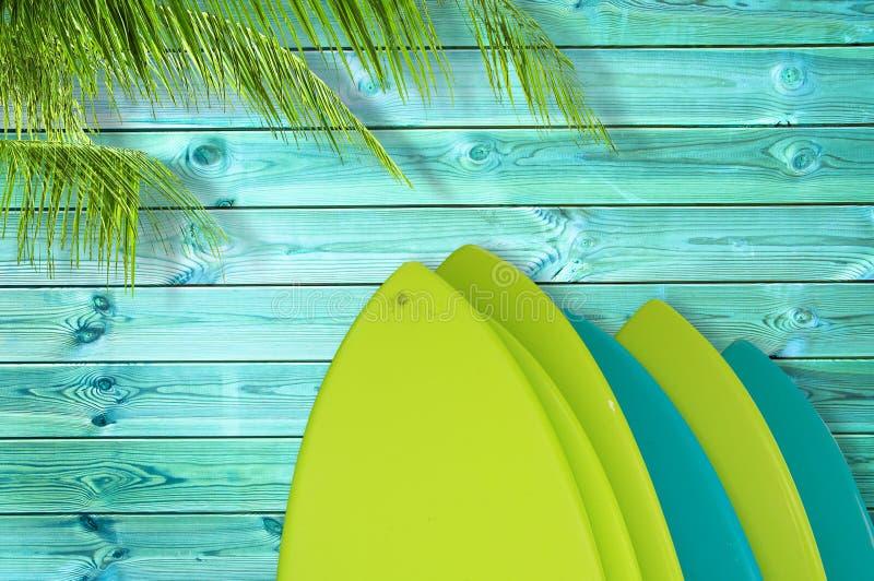 堆在热带蓝色木板条背景的五颜六色的冲浪板与棕榈树 库存照片