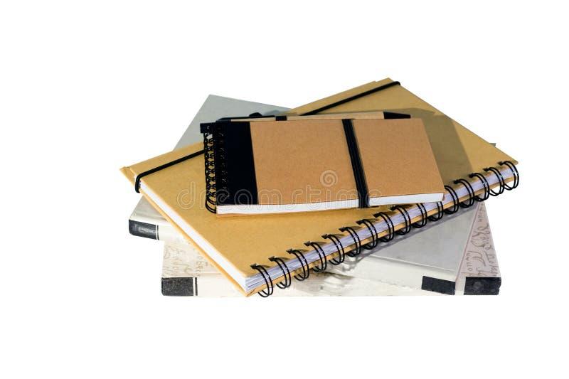 堆在白色背景或棕色笔记本隔绝的圆环包扎工具书 库存照片