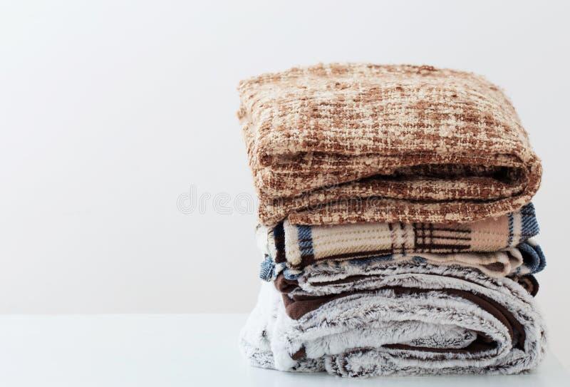 堆在白色背景的毯子 免版税库存照片
