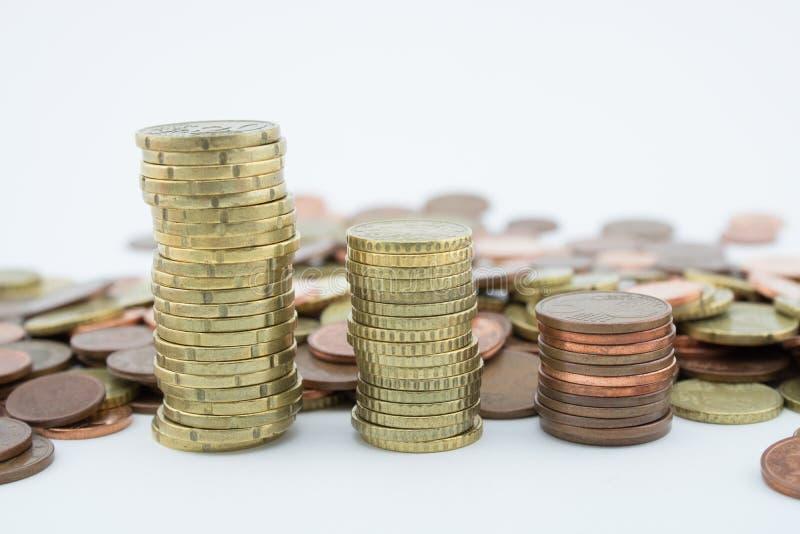 堆在白色背景的金黄和古铜色硬币 二十欧分硬币  免版税库存照片