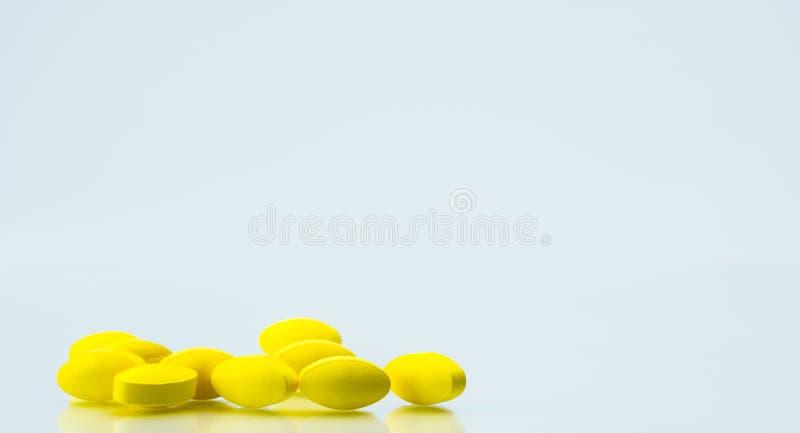 堆在白色背景的黄色卵形片剂药片与文本的拷贝空间 温和减轻痛苦管理 止痛药军医 免版税库存照片