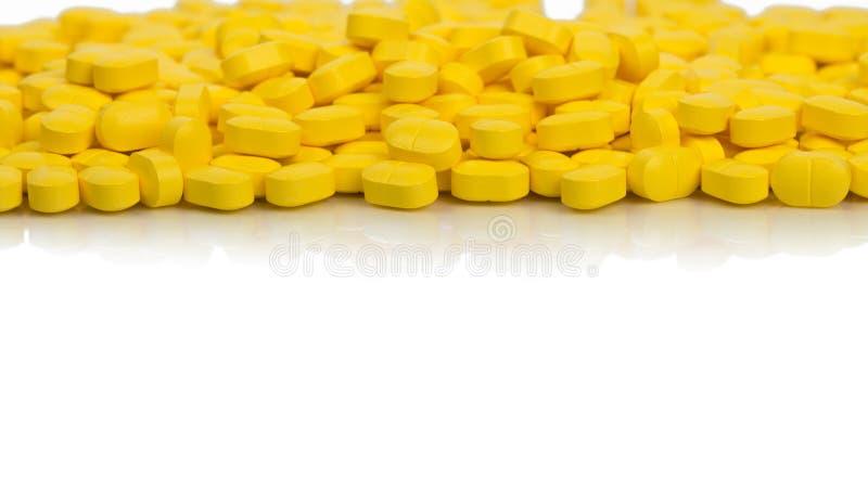 堆在白色背景的黄色卵形长方形形状片剂药片与拷贝空间 安心痛苦的医学 免版税库存照片