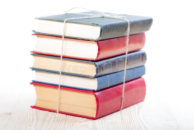 堆在白色背景隔绝的木桌上的书 回到学校 复制空间 图库摄影