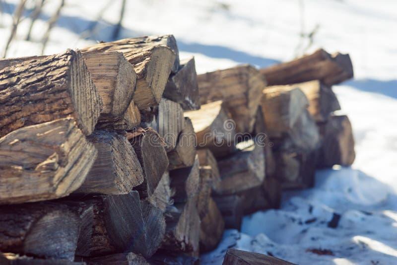 堆在积雪的地面的分裂木柴 库存图片