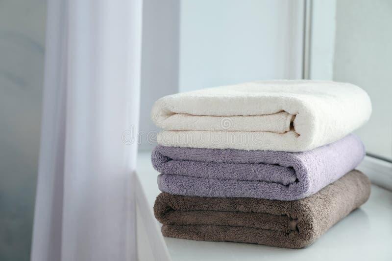 堆在窗台的新鲜的毛巾 免版税图库摄影