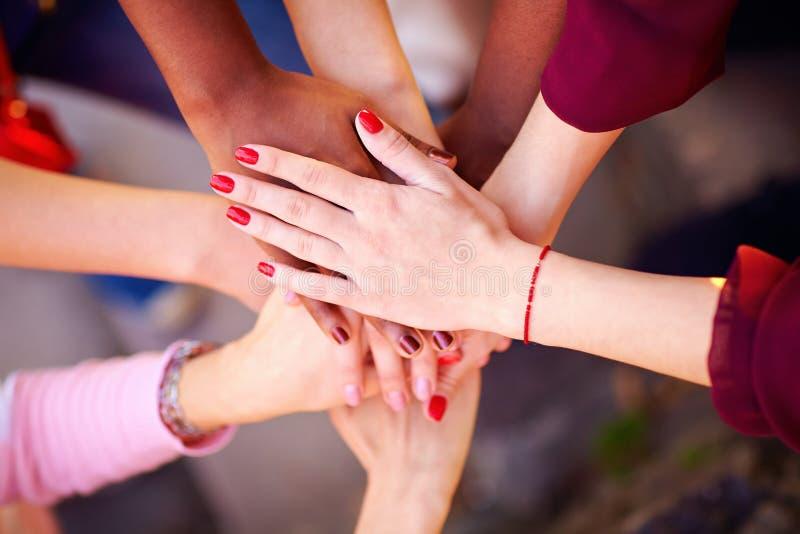 堆在联合标志的女性不同种族的手 免版税库存照片