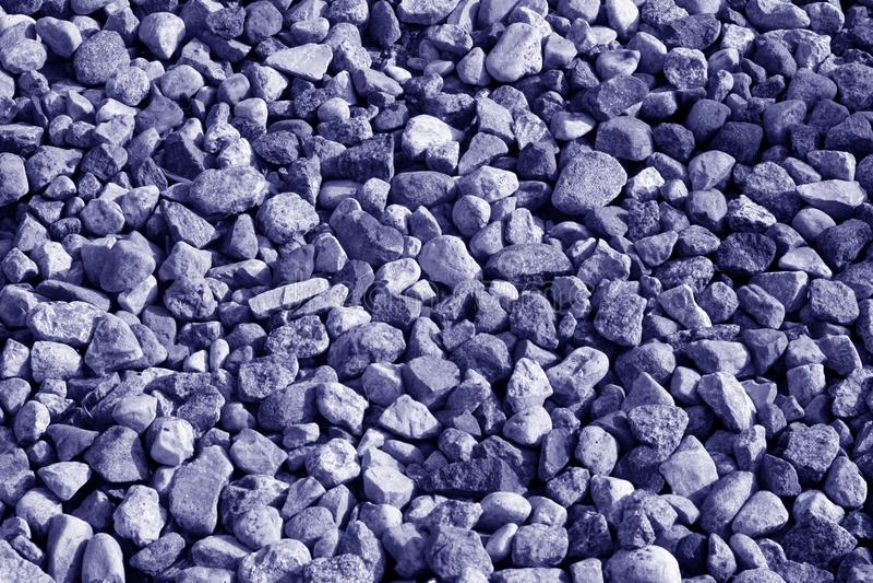 堆在蓝色颜色的石渣石头 免版税库存照片