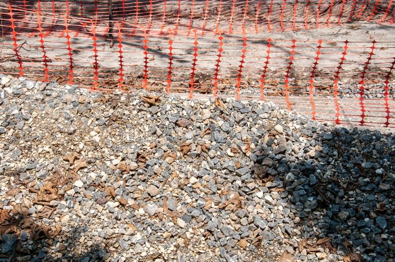 堆在街道建造场所的石渣有橙色安全网或篱芭接近的 库存图片