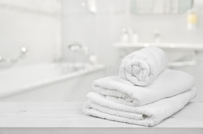 堆在被弄脏的卫生间背景的被折叠的白色温泉毛巾 免版税库存图片