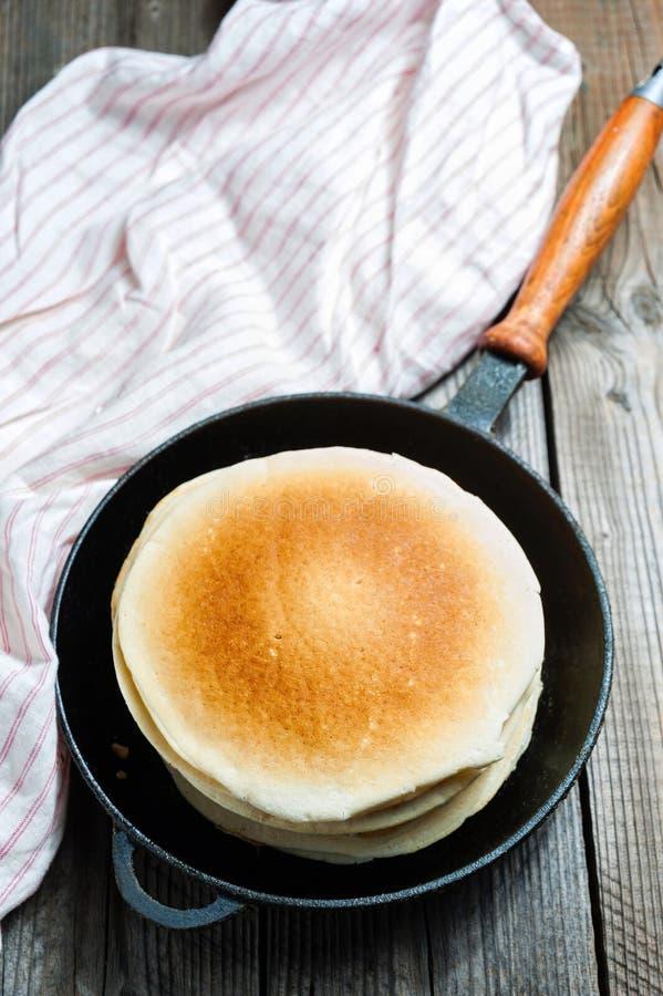 堆在铸铁煎锅的薄煎饼 顶视图 免版税库存照片