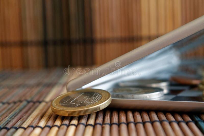 堆在镜子的欧洲硬币反射在广角背景衡量单位是1 ero的木竹桌上的钱包谎言 库存照片
