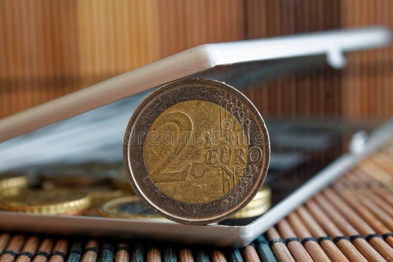 堆在镜子的欧洲硬币反射在木竹桌背景衡量单位的钱包谎言是2欧元 免版税库存图片