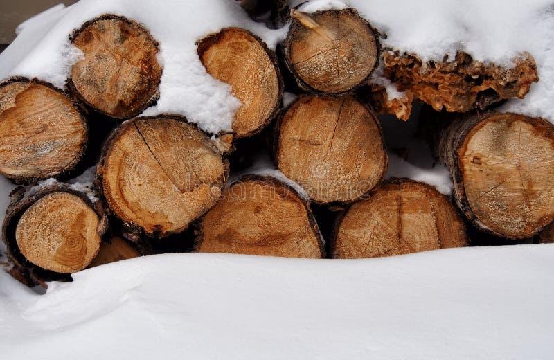 堆在雪的木头 免版税库存图片
