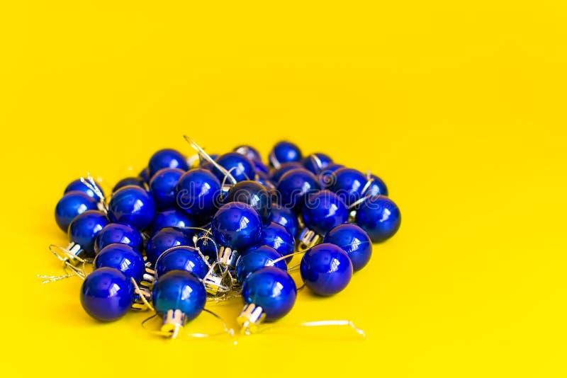堆在黄色背景的蓝色圣诞节球 库存图片