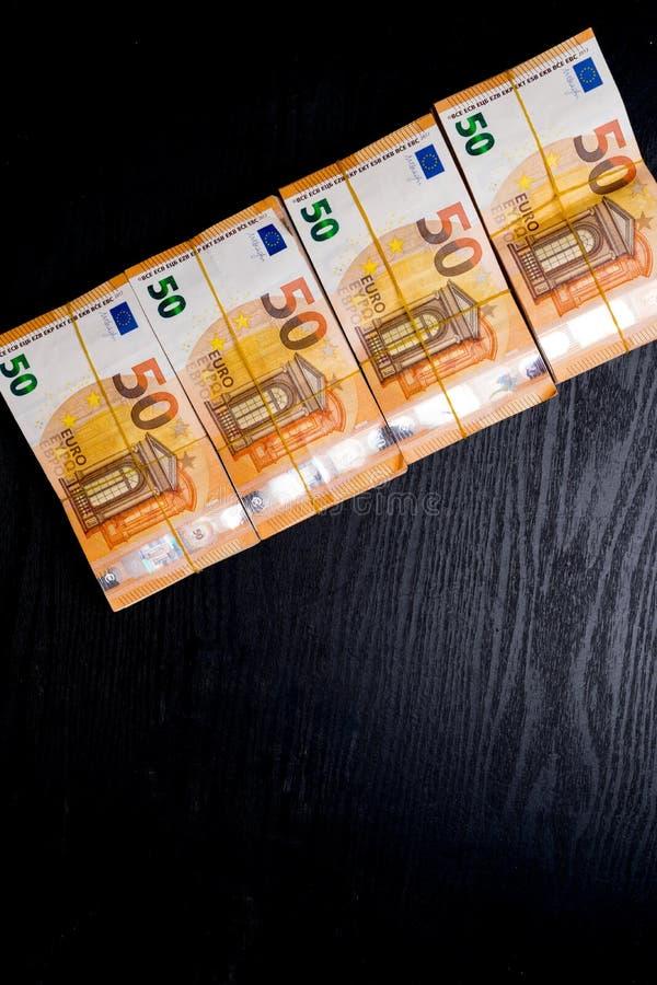 堆在黑色隔绝的橡皮筋儿下的50张真正的欧元笔记50欧元钞票 大约20000欧元价值 免版税库存图片