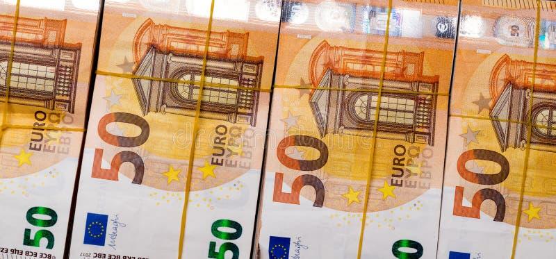堆在黑色隔绝的橡皮筋儿下的50张真正的欧元笔记50欧元钞票 大约20000欧元价值 免版税库存照片