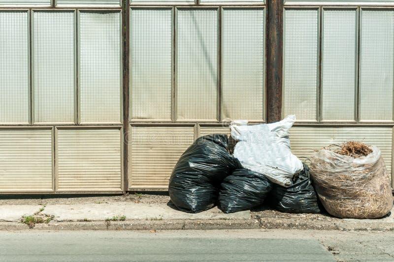堆垃圾和家庭破烂物在房子的前面离开街道的在倾销者卡车的塑料袋能收集 库存照片