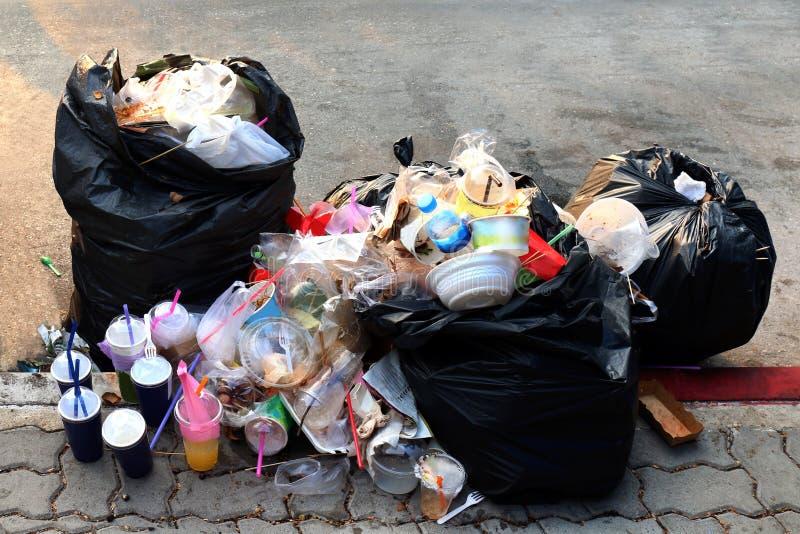 堆垃圾塑料黑色和垃圾袋浪费许多在小径、污染垃圾、塑料废物和袋子泡沫盘子垃圾 免版税库存照片