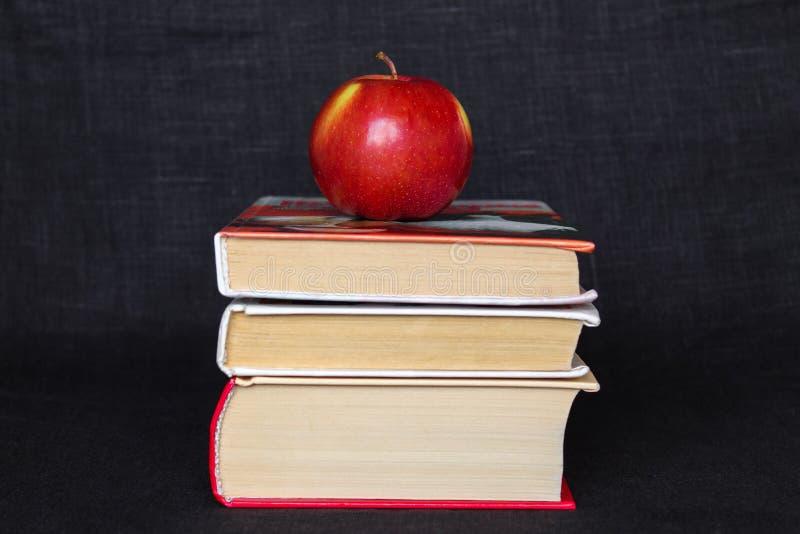 堆堆书用在上面的红色苹果,回到学校概念,教育概念,拷贝文本空间,黑背景 免版税库存图片